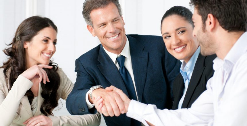 Mature businessman shaking hands to seal a deal with his partner and colleagues in a modern office
